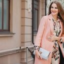 Portrait of attractive stylish smiling woman walking city street in pink coat and floral dress Free Photo