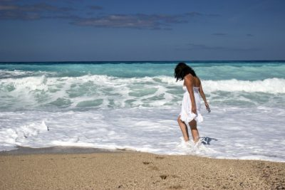 A person in a white dress on a beach Description automatically generated with low confidence